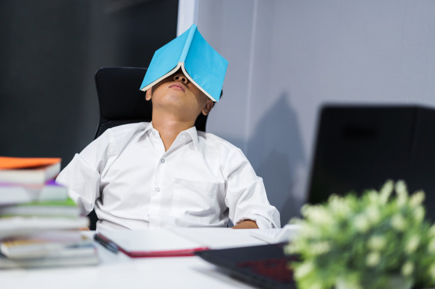 estudiante-dormido-escritorio-libro-cara